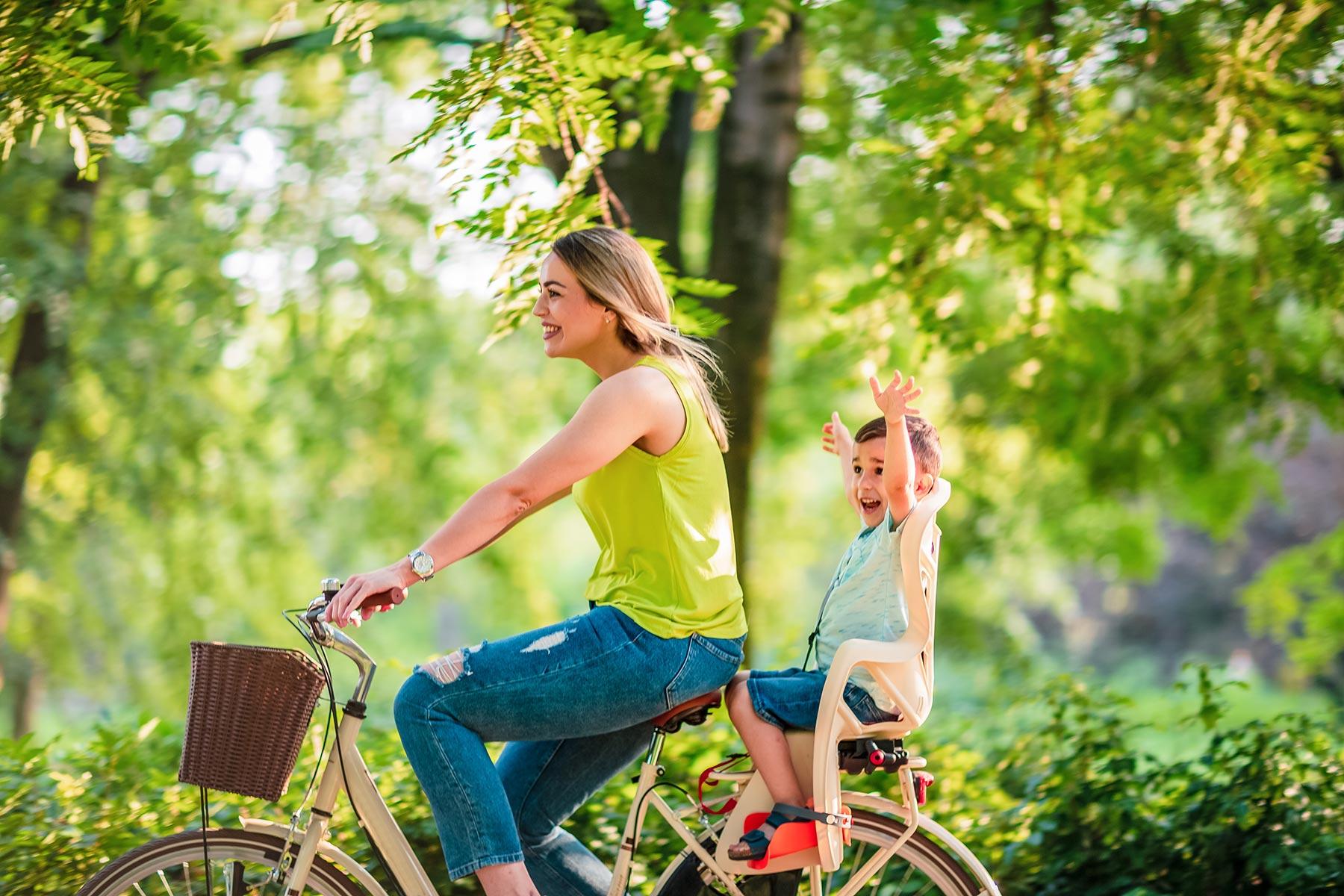 Maman à vélo avec son enfant sur le porte-bagage qui lève les bras au ciel